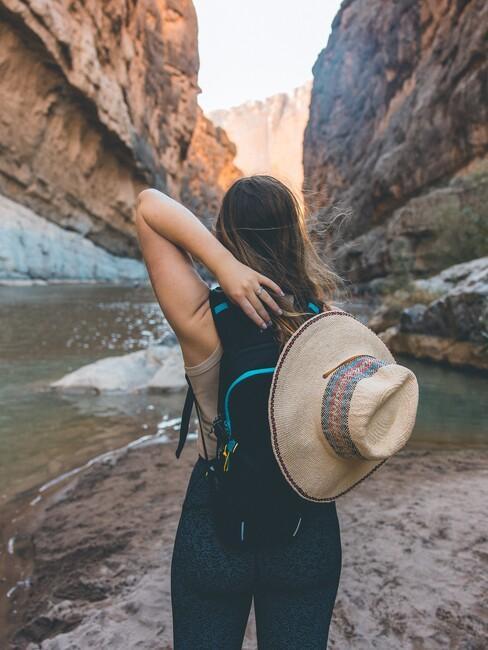 vrouw in het midden van rotsen met een rieten hoed