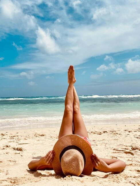vrouw op het strand met een rieten hoed