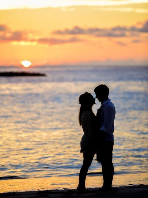 bruidspaar op het strand voor de zonsondergang