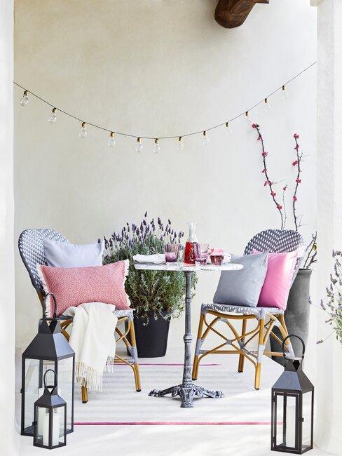 tuin decoreren met lichtslichters en stoelen en lantaarns