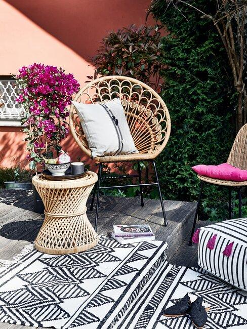 tuin met vloerkleed en rieten stoel
