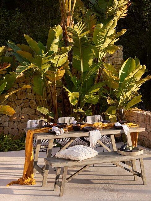 gedekte houten buitentafel met plant