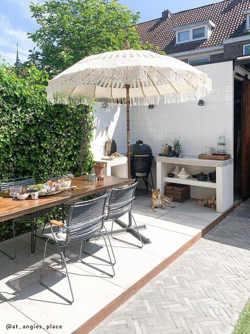 een buitenkeuken met parasol en houten tafel