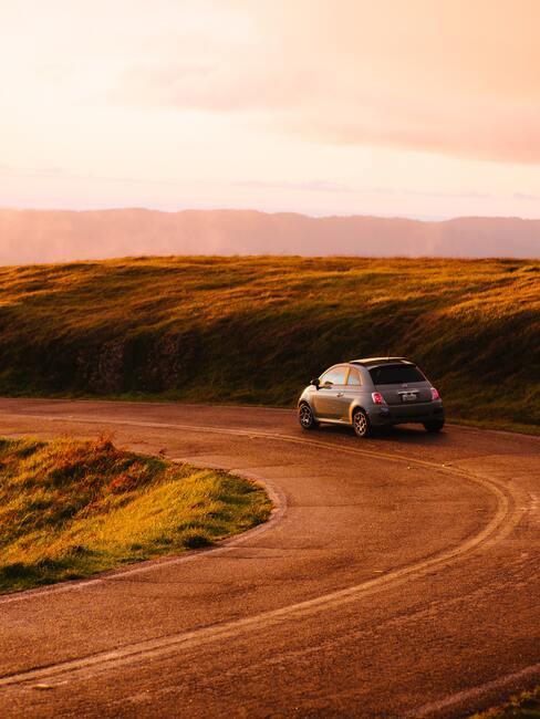 grijze Fiat 500 op een landweg