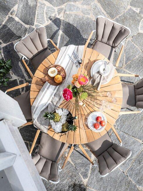 terras met grijze stenen en houten tafel