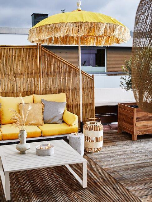 terras met houten planken en gele parasol en witte bank