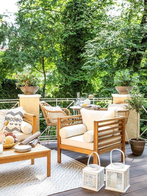houten tuinset met gele kussens en witte lantaarns
