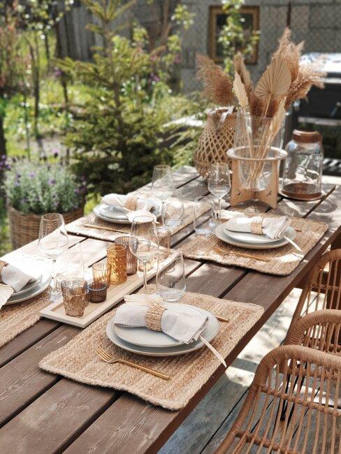 houten buitentafel gedekt met rieten placemats