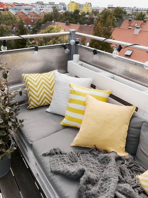 balkon met loungebank en gele kussens