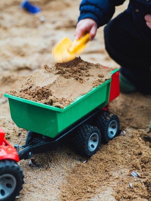 zandbak met speelgoed wagentje voor een kindvriendelijke tuin