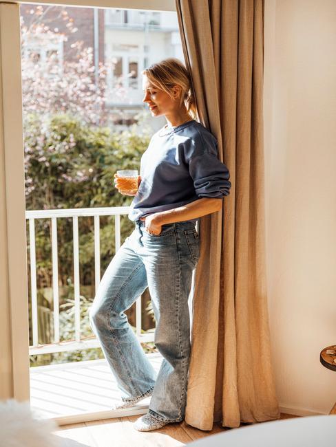 vrouw in de deuropening met toupe gordijnen en witte koffiemok