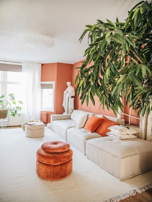 oranje woonkamer met grijze bank en wit kleed