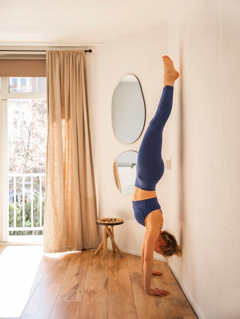 vrouw in een handstand tegen de muur