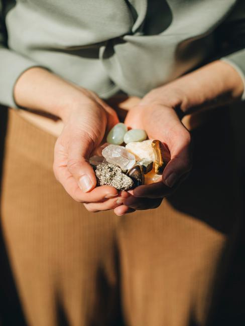 vrouw die stenen in haar hand vast heeft