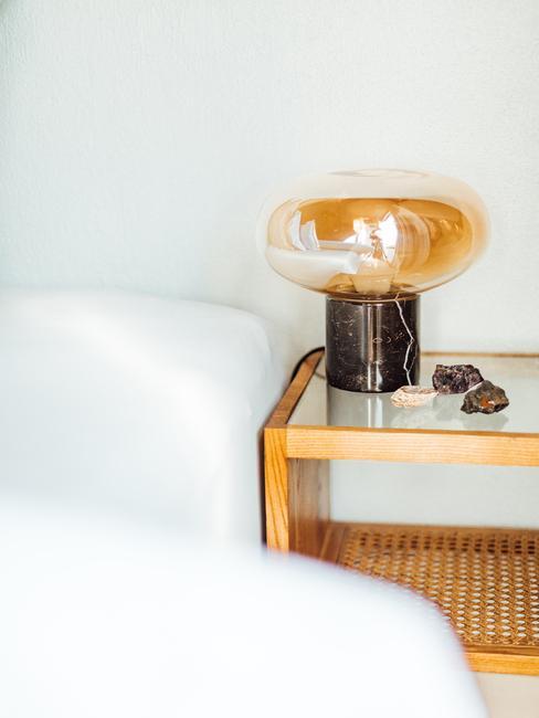 wit bed met houten nachtkastje en speciale lamp