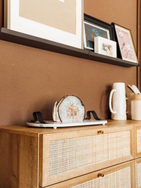 bruine muur met houten kast en fotolijsten