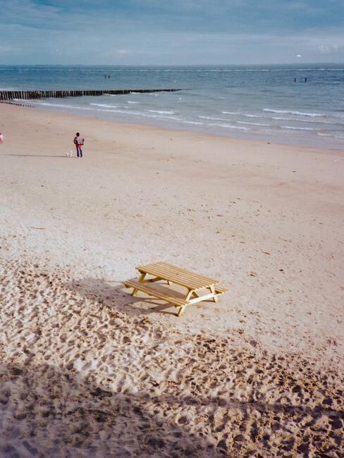 strand met houten picknick tafel