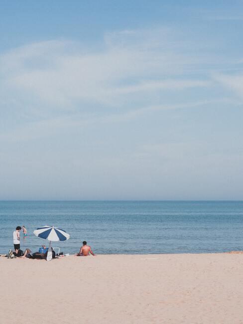 mensen op het strand met een blauw/witte parasol