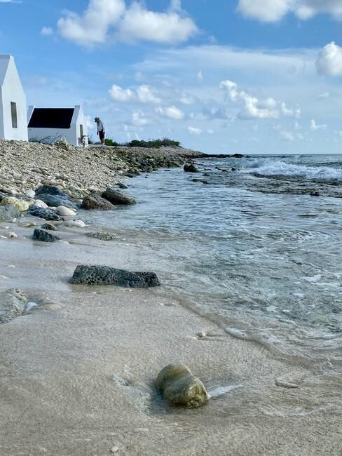 huisjes aan het water met een strand en rotsen