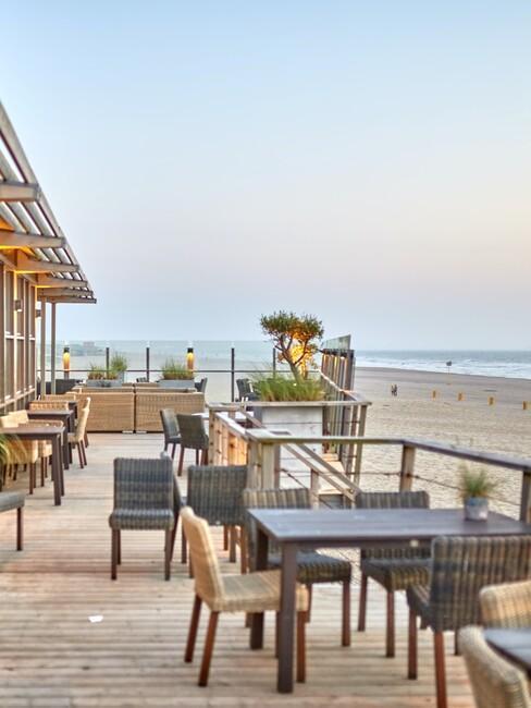 een terras aan het strand met een houten vlonder