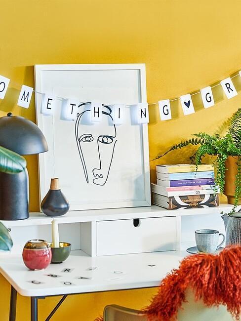 gele muur met wit bureau