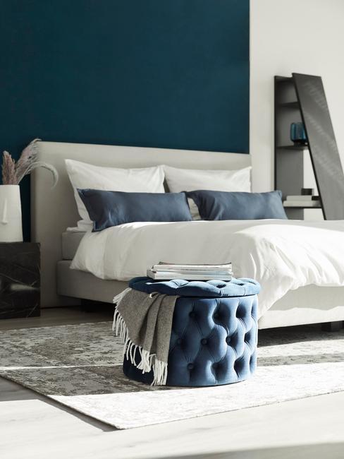 donkerblauwe muur met grijs bed en blauwe sierkussens