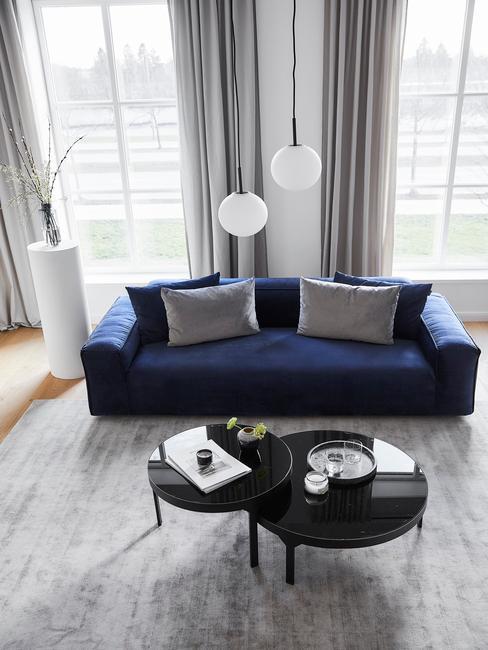 donkerblauwe bank met zwarte tafel en grijze sierkussens