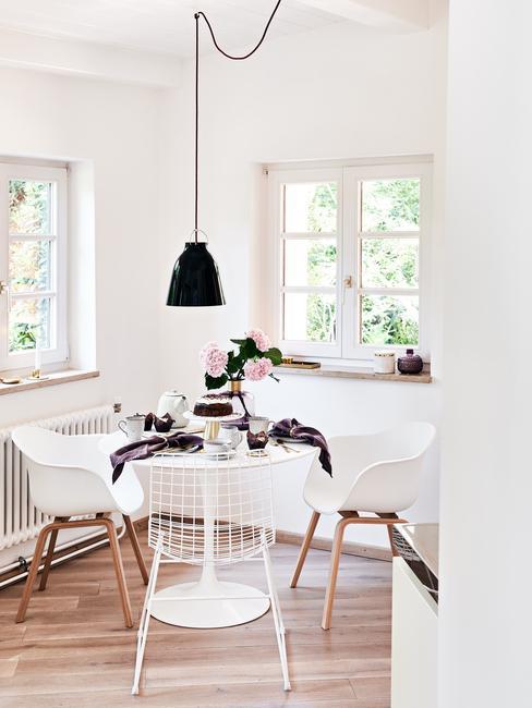 witte tafel en stoelen met een zwarte lamp