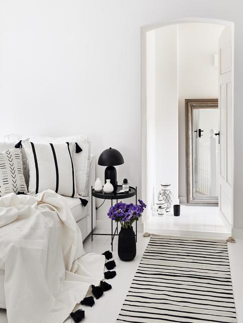 wit bed met paarse detals en zwart wit vloerkleed