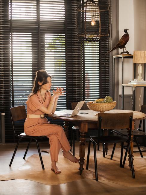 maria-elena op een zwarte stoel aan een houten ronde tafel