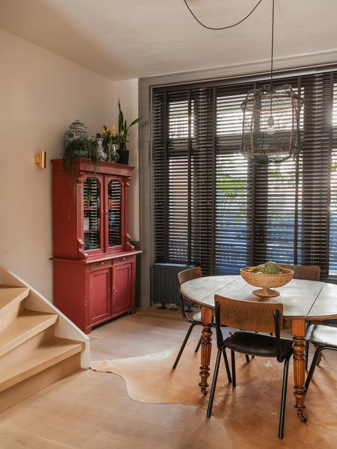 beige kamer met houten vitrine kast en houten ronde tafel