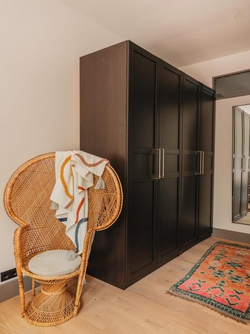 zwarte kledingkast met grote rieten stoel