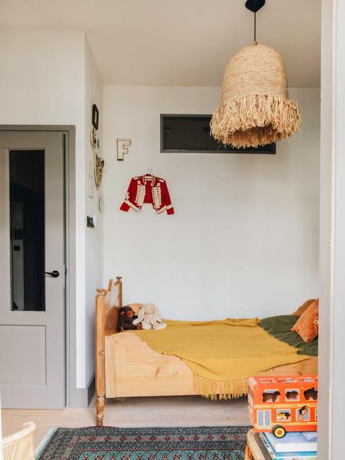 houten kinderbed met gele dekens en rieten hanglamp