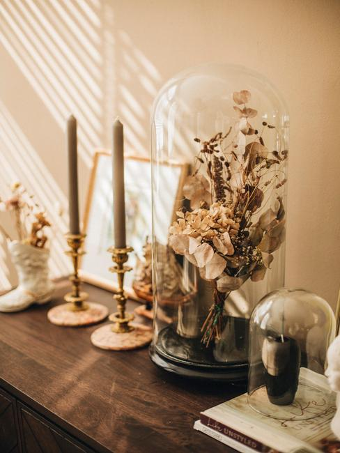 houten blad met gouden kaarshouders en droogbloemen