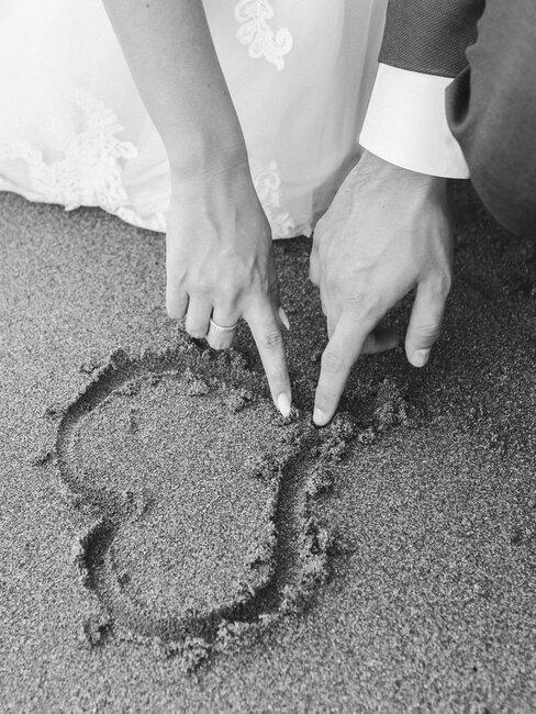 echtpaar tekent hart in zand