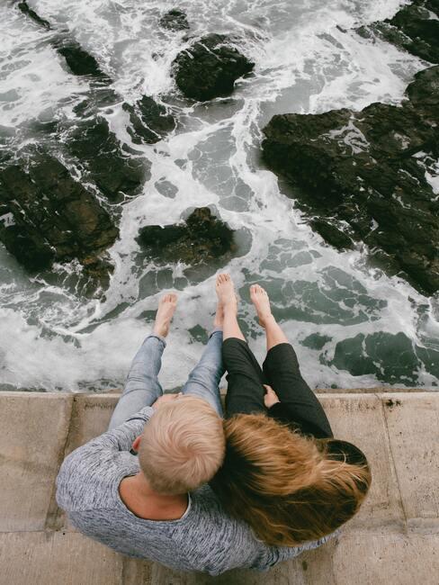 stel op de kade kijkend naar de zee