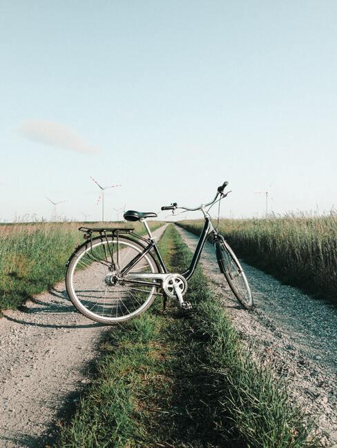 fiets op een landweg omringt door weilanden