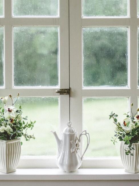 witte theepot en witte vazen met bloemen voor een raam met een ruiten witte kozijn
