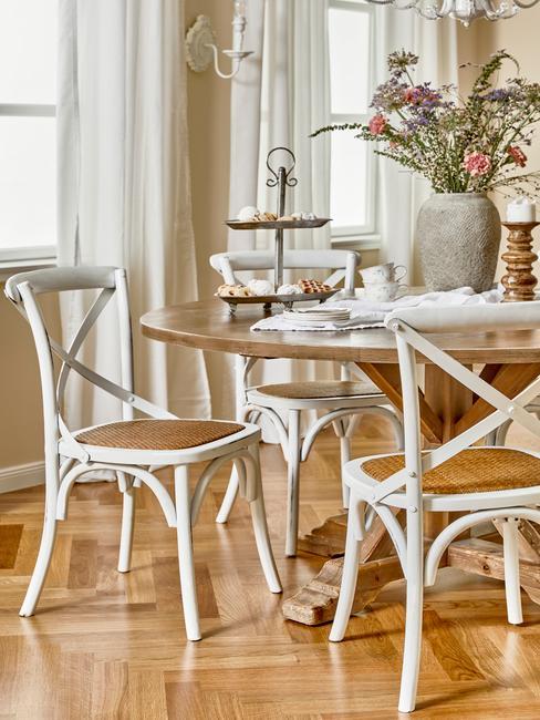 houten tafel met witte stoelen en een grijze vaas met veldbloemen