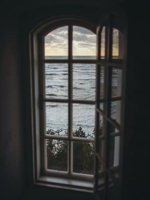 raam met witte kozijnen met uitzicht op zee