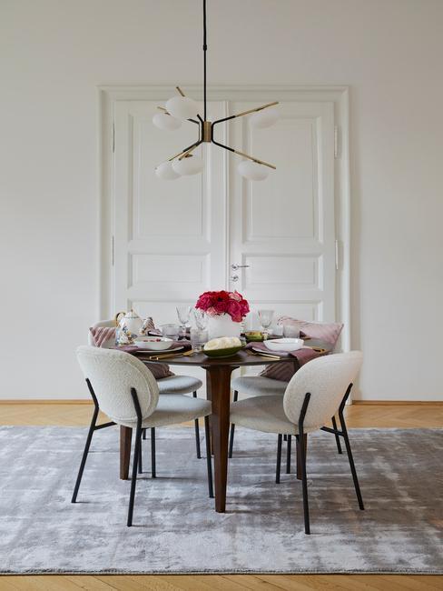 een witte deur met grijs vloerkleed en witte stoelen