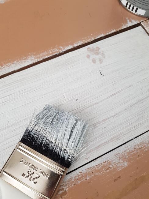 kwast met witte verf op hout