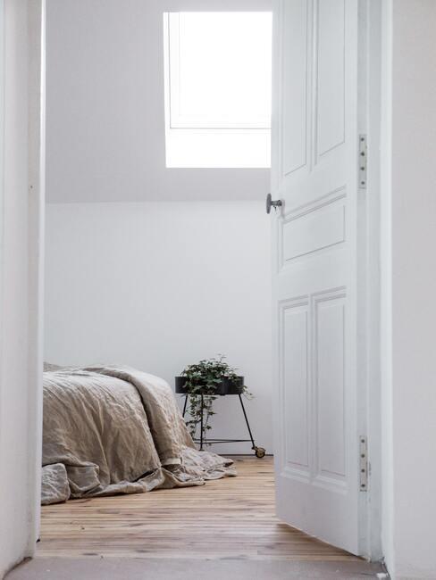 witte deur met een bed met een toupe deken