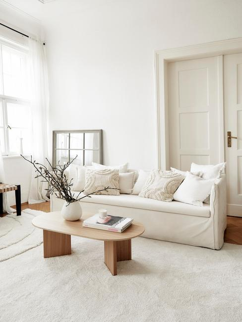 witte bank met beige kussens en houten bijzettafel
