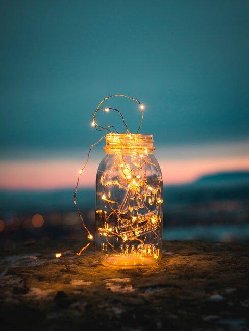 mason jar met verlichting op een rots