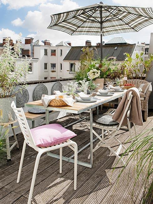 witte tafel en stoelen met gestreepte parasol en roze kussens