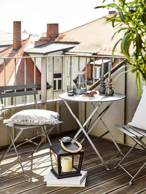 grijze balkonset met witte kussens op een houten balkonvloer