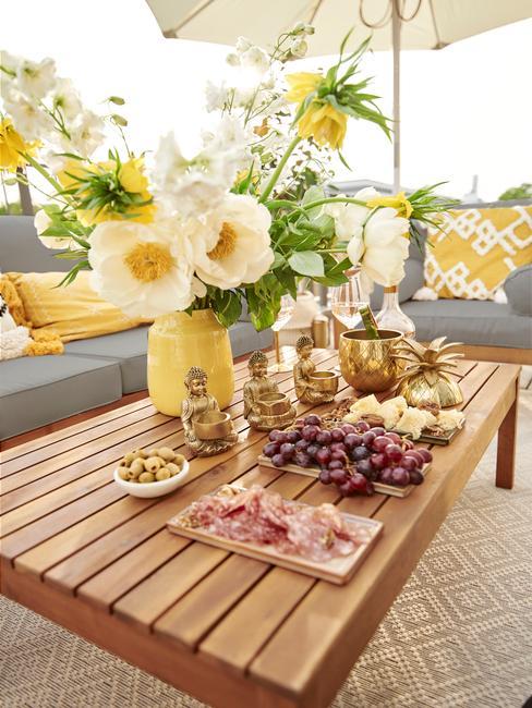 houten tafel met gele vaas op een outdoor vloerkleed