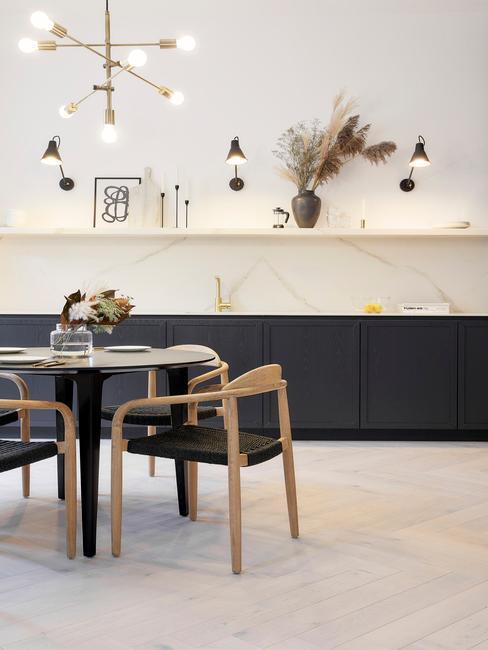 zwarte keuken met ronde tafel en houten stoelen