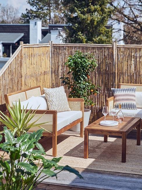 dakterras inrichten met houten tafel en bamboescherm